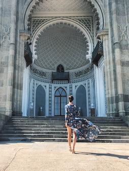 Ragazza che entra e un bellissimo edificio a mosaico in una giornata di sole.