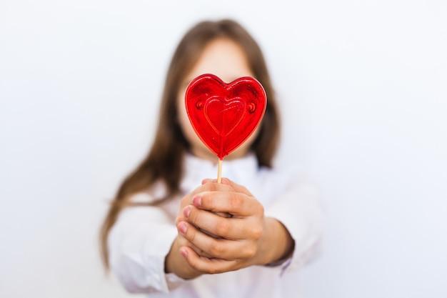 Una ragazza di aspetto europeo su uno sfondo bianco tiene in mano una lecca-lecca a forma di cuore, amore, regalo, famiglia, san valentino