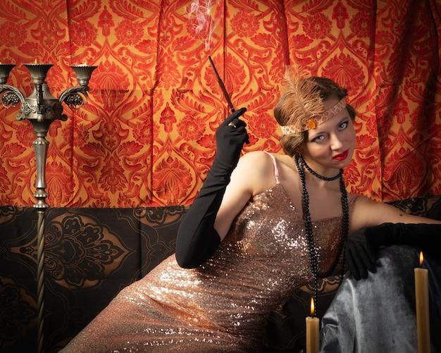 Ragazza in abito da sera con una sigaretta. studio fotografico in stile retrò