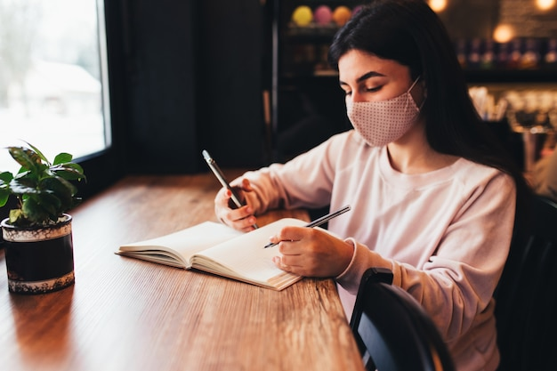 Ragazza in maschera facciale, lettura del telefono e scrittura sul taccuino.