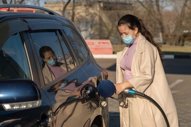 Ragazza con una maschera protettiva per il viso che fa rifornimento di benzina all'auto