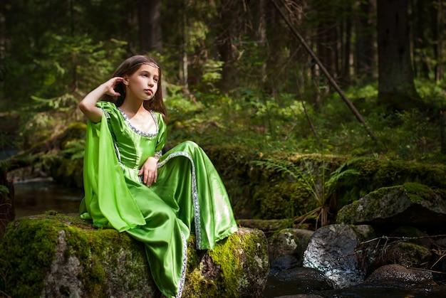 La ragazza in un abito da elfo da favola siede a piedi nudi sulle antiche rovine nella foresta vicino al ruscello