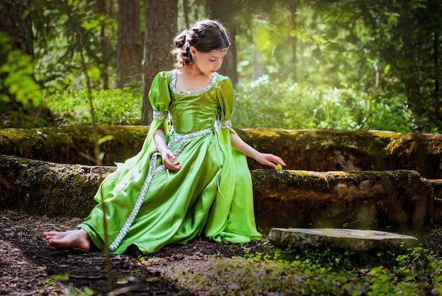 La ragazza in un abito da elfo da favola siede a piedi nudi sulle antiche rovine nella foresta, giocando con una farfalla