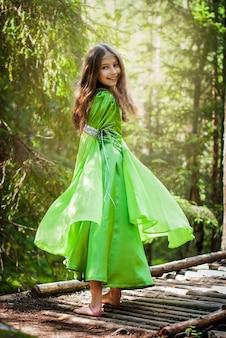 La ragazza in un vestito da elfo da favola cammina a piedi nudi lungo un sentiero nel bosco, voltandosi