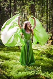La ragazza in un vestito da elfo da favola cammina a piedi nudi attraverso la foresta sbattendo le ali