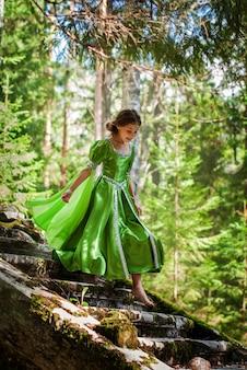 La ragazza in un vestito da elfo da favola cammina a piedi nudi attraverso la foresta scendendo le rune di un'antica scala