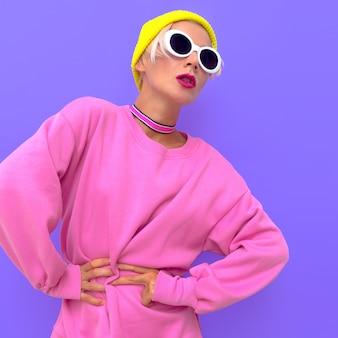 Ragazza in accessori moda beanie cap occhiali da sole e girocollo vibrazioni urbane colorate alla moda di strada