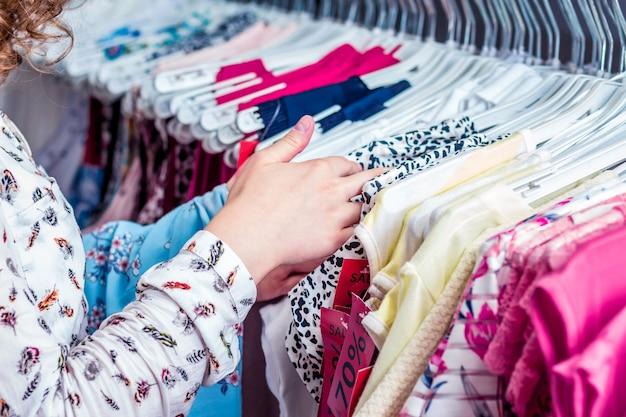 La ragazza nel negozio di moda sceglie una camicetta per l'estate