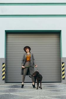 La ragazza in abiti alla moda e indossa un cappello è in piedi con un cucciolo al guinzaglio