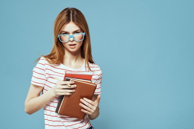 Ragazza in occhiali alla moda con i notebook in mano su una vista ritagliata blu copy space.