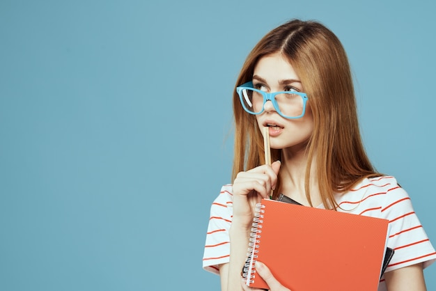 Ragazza in occhiali alla moda con i taccuini in mani su un muro blu ritagliata vista lo spazio della copia.