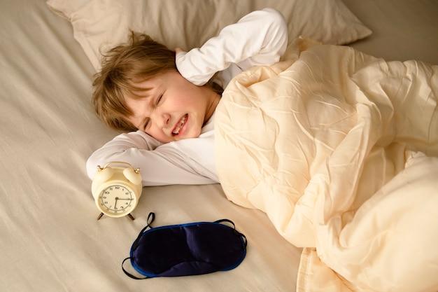 Una ragazza una bambina è impertinente infelice si coprì le orecchie con le mani quando la sveglia suona forte al mattino rifiutandosi di alzarsi presto la mattina