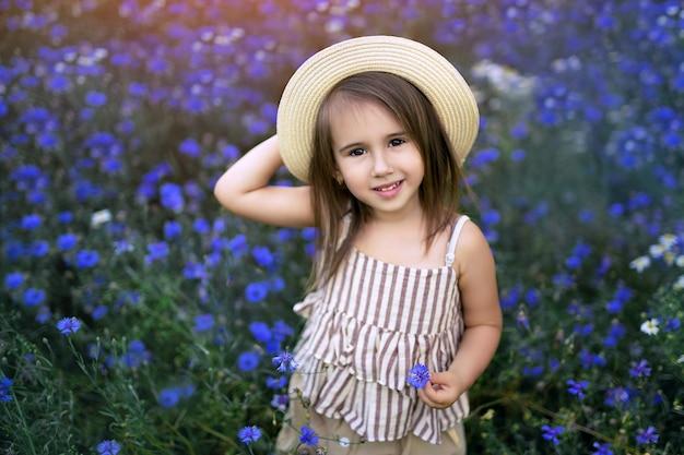 Una ragazza in un campo di fiordalisi in fiore.