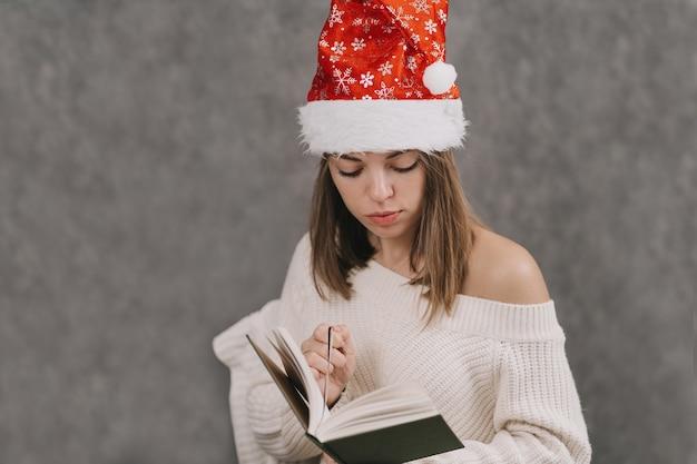 La ragazza compila il suo diario. l'uomo pratica il potere del pensiero. esprimi un desiderio per il nuovo anno. crea un elenco di regali per amici e familiari