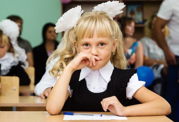 Ragazza di prima elementare seduta a una scrivania durante la prima lezione