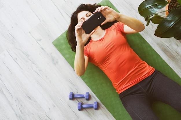 Una ragazza sul pavimento guarda la formazione online del telefono