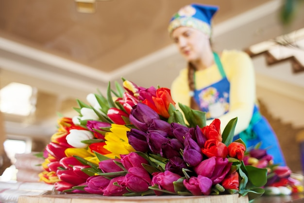 Il fiorista della ragazza sta imballando i bei tulipani in un negozio di fiore in carta kraft