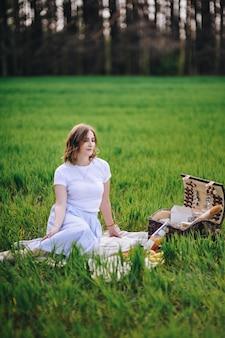 Ragazza nella foresta ad un picnic. si siede su una radura, erba verde. bl