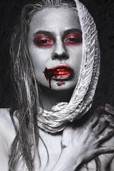 Ragazza a forma di zombi, cadavere di halloween con sangue sulle labbra