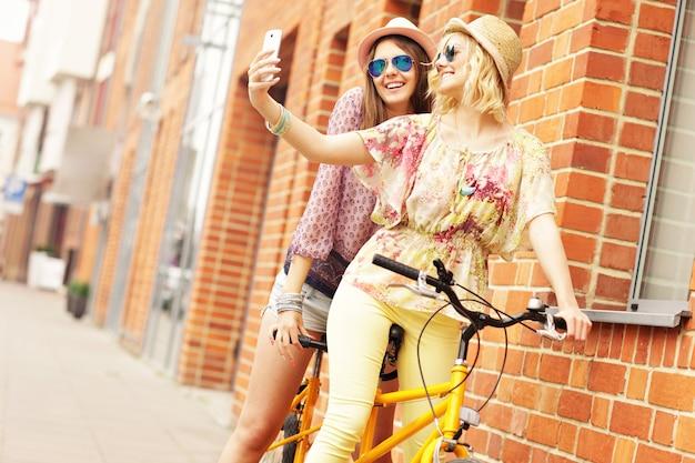 Amiche in sella a una bicicletta tandem e facendo selfie in città
