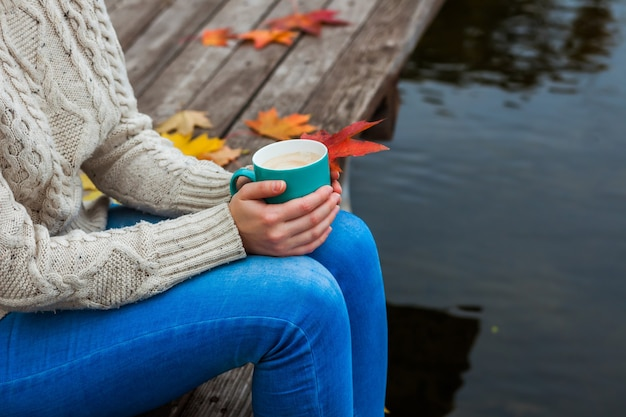 La ragazza si bloccò e teneva in mano una tazza di caffè caldo. foglie d'autunno. blu, rosso, giallo freddo.