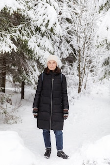 Ragazza in una pelliccia in un bosco innevato