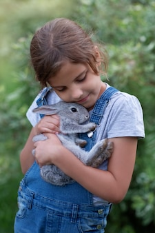 Una ragazza in giardino con un coniglio