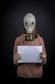 La ragazza con una maschera antigas su uno sfondo nero tiene un lenzuolo bianco, da vicino. il tuo testo qui.