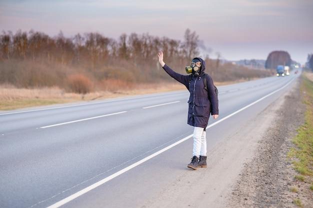Una ragazza con una maschera antigas sulla strada alza la mano e cerca di fermare le auto