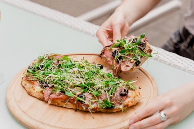 La ragazza prende in mano la pinsa romana. cucina gourmet italiana. scrocchiarella. pinsa con peperoni, pomodori, formaggio, microgreen.