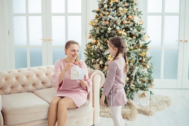 Ragazza che fa un regalo di natale alla mamma
