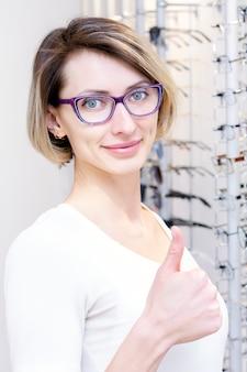 Ragazza con gli occhiali per la vista. provare gli occhiali in un negozio di ottica. la ragazza soddisfatta mostra come.