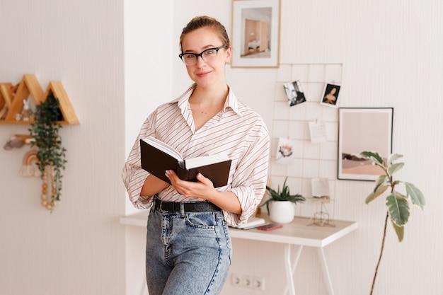 Ragazza con gli occhiali a casa con un libro