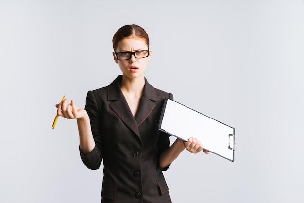 Una ragazza con gli occhiali e un rigoroso abito grigio tiene in mano carta e penna e guarda con rabbia