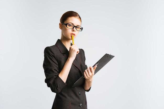 Una ragazza con gli occhiali e un abito rigoroso esamina attentamente i documenti