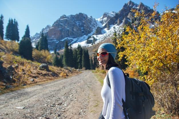 Una ragazza con gli occhiali cammina in montagna. la strada in montagna.