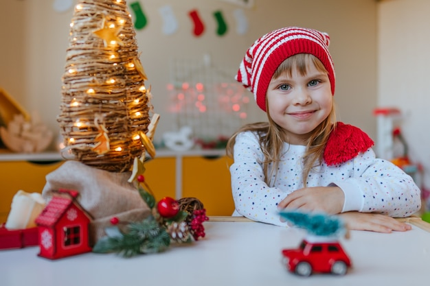 Ragazza con cappello gnomo decorato albero di natale vite con pezzi di arancia secca nella stanza dei bambini