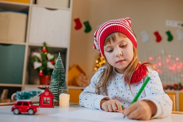 Ragazza con cappello da gnomo che scrive una lettera a babbo natale al tavolo nella stanza dei bambini