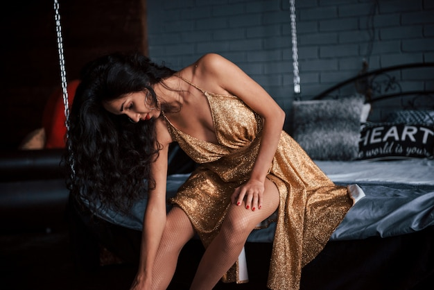 La ragazza in vestito dorato si siede al letto bianco sulle catene in appartamenti di lusso