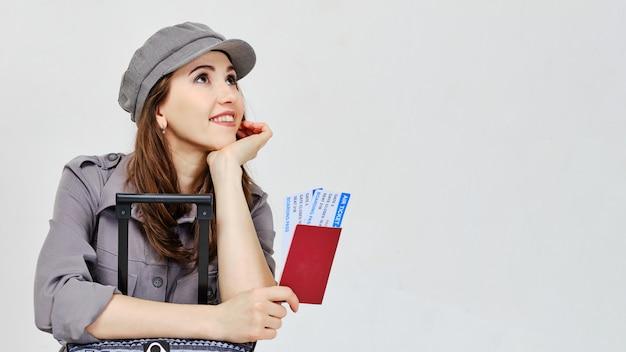 Una ragazza in un abito grigio con bagagli e biglietti aerei con un passaporto distoglie lo sguardo.