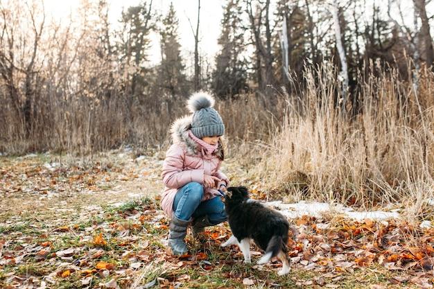 Ragazza con un cappello grigio e una giacca calda con un cucciolo di cani cammina nella foresta autunnale, alberi ed erba