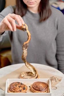 Una ragazza con un maglione grigio tiene in mano un panino smontato con semi di papavero