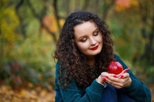 Ragazza con un maglione verde e una mela in mano nella foresta autunnale