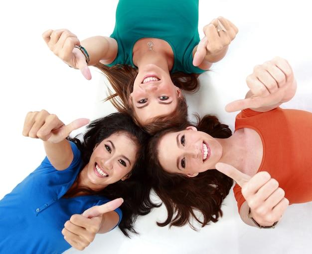 Gruppo della ragazza che si trova sul pavimento che mostra pollice in su