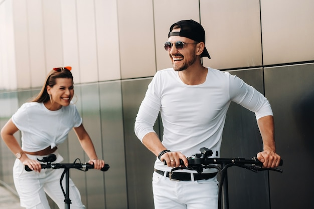 Una ragazza e un ragazzo stanno camminando su scooter elettrici per la città, una coppia innamorata su scooter.