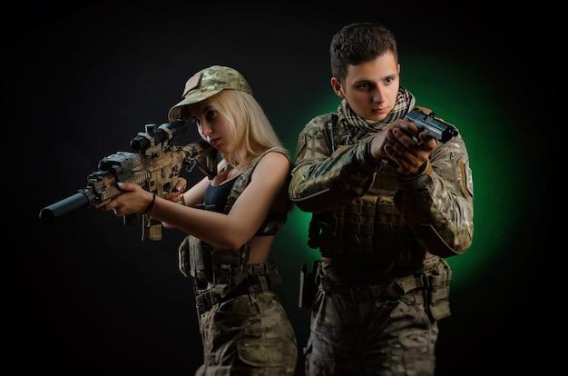 Una ragazza e un ragazzo in tuta militare posano con una pistola softair su uno sfondo scuro