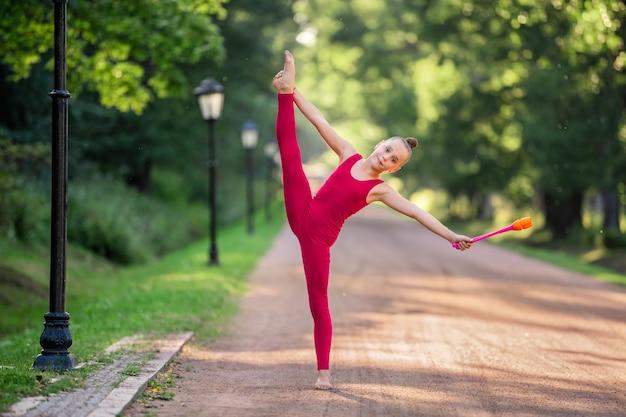 Ginnasta ragazza in tuta rosso brillante facendo un esercizio con i club nel parco in una calda serata soleggiata