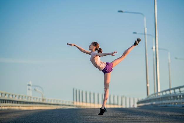 Ginnasta ragazza impegnata in estate per strada, su uno sfondo di cielo blu, spago, stretching, arabesco