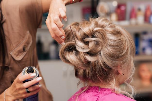 La ragazza-parrucchiera fa al cliente un'acconciatura per una festa. il parrucchiere aggiusta tutto con la lacca
