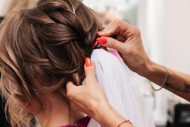 Una ragazza-parrucchiera realizza l'acconciatura di una cliente per la celebrazione fissando le ciocche con forcine e forcine.